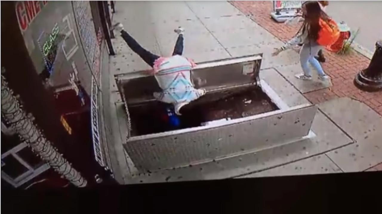 Por andar en el celular… mujer cae en hoyo en la calle